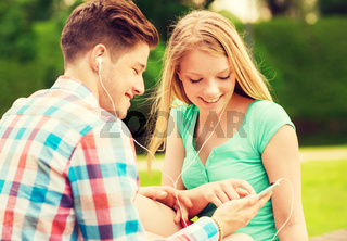 smiling couple with smartphone and earphones