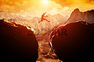 Man jumping over precipice between two rocky mountains at sunset. Freedom