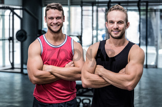 Two smiling muscular men with arms crossed