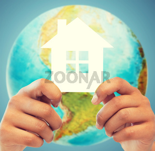 couple hands holding green house over earth globe