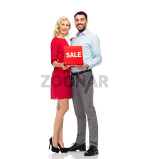 happy couple with red sale sign