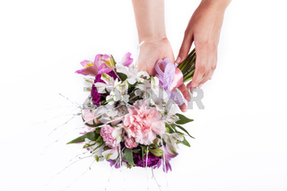 Hands holding a bouquet from pink and purple gillyflowers and alstroemeria on white