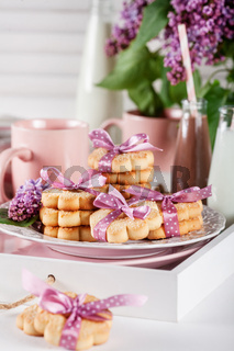 Cookies on a white tray with mugs, chocolate milkshakes and lilac flowers