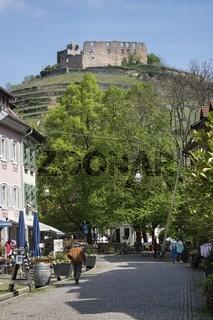 Fußgängerzone in der historischen Altstadt von Staufen mit der Burg Staufen
