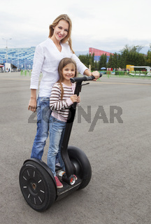 Happy young caucasian woman and her daughter on the segway