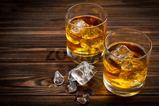 Two glasses with ice and whiskey
