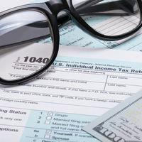 US 1040 Tax Form, glasses and dollars - studio shot