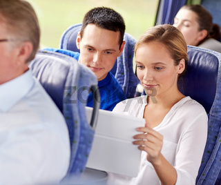 happy couple with tablet pc in travel bus