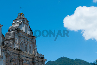 White Big Church Beside in front of mountains under blue sky with one cloud