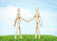Two friends shake hands to each other. Abstract image with wooden puppets