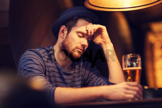 unhappy lonely man drinking beer at bar or pub