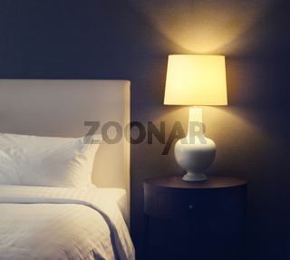 Hotel bedroom with lamp and hotel bed with space for text