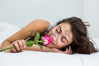 Woman smelling a rose flower on bed