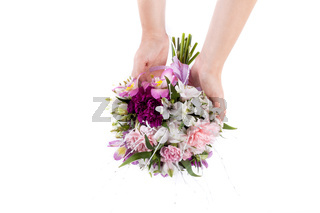 Hands holding a summer bouquet from pink and purple gillyflowers and alstroemeria on white