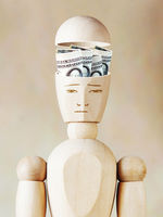 Many dollar banknotes lie in the human head. Abstract image with wooden puppet
