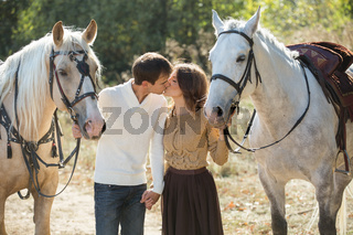 Young couple walking in a picturesque place with horses