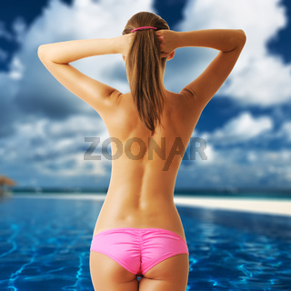 Woman topless at tropical swimming pool