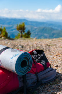 Closeup Red Backpack With sleeping mat Lays on rocky ground in front of mountain Tajamulco and blue sky with clouds