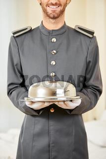 Freundlicher Page serviert Essen mit Speiseglocke