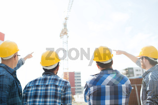 group of builders in hardhats at construction site