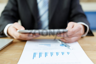 businessman checking financial reports on table
