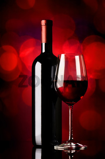 Bottle with wine on red