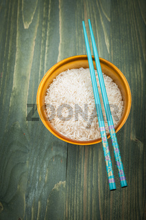Uncooked rice grains in wood bowl