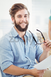 Portrait of smiling man holding eyeglasses and paper