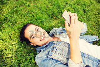 smiling young girl with smartphone lying on grass