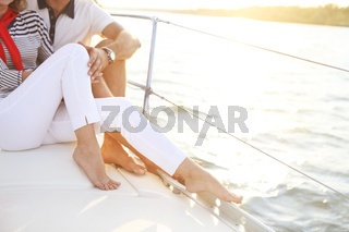 Feet of a couple stting on sailboat deck in the sea