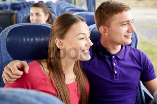 happy teenage couple or passengers in travel bus