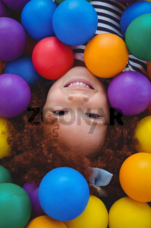Cute smiling girl in sponge ball pool