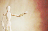 Wooden puppet points aside with its hand. Conceptual image about presentation
