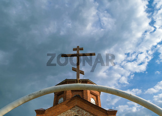 White semi-circular arch of iron pipe with dark Orthodox cross over it before the tower of the ancient temple of bricks against the blue sky with clouds
