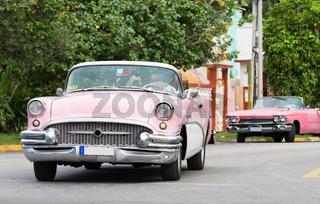 Rosaner Oldtimer fahrend in Kuba Varadero