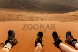 Enjoying landscape and resting after climbing red sand dune in desert. Namibia