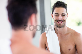 Handsome shirtless man looking in the mirror