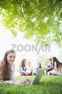 Happy student using her laptop outside