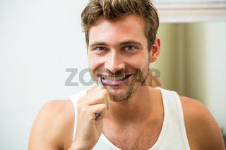Young man brushing teeth