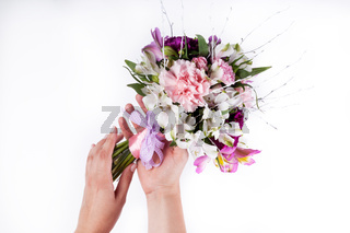 Hands holding a pastel bouquet from pink and purple gillyflowers and alstroemeria on white background
