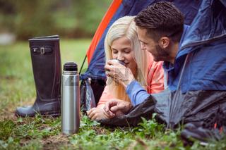 Happy couple lying in tent having hot drinks