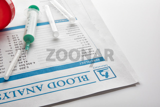 Blood test report with vials urine container and syringe elevated