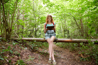 happy woman with backpack and tablet pc in woods