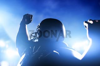 American football player celebrating score and victory. Night stadium lights
