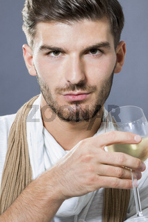 Sexy handsome man drinking white wine