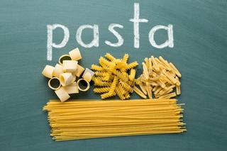 various uncooked pasta on chalkboard