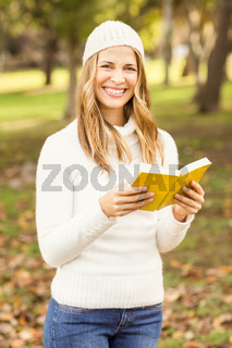Portrait of a smiling pretty woman reading a book