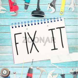 Fix it against tools and notepad on wooden background