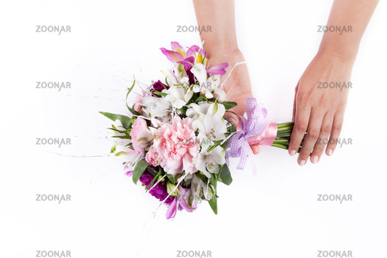 Hands holding a pink bouquet from gillyflowers and alstroemeria on white background