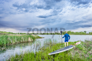 senior paddler with SUP paddleboar watching stormy sky